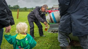 A young child watches while a man pours a pint of beer from the keg.